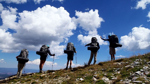 Five People Standing on a Mountain With Backpacks