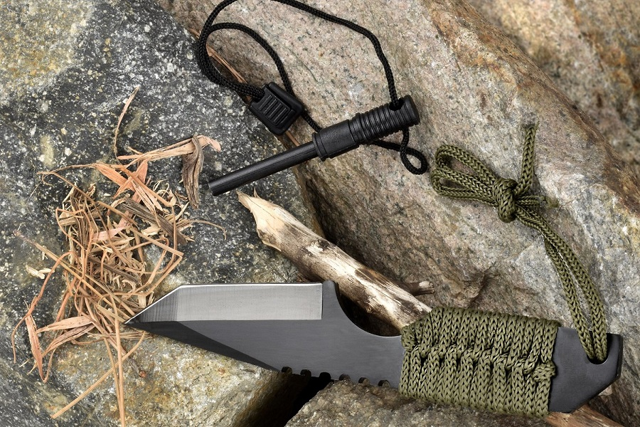 SE KHK6320 Outdoor Tanto Knife with Fire Starter on a Rock