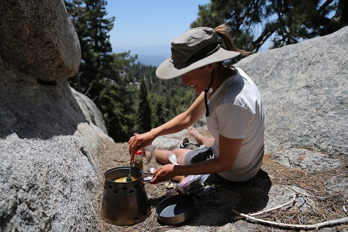 Female Backpacker Cooking on Rocks