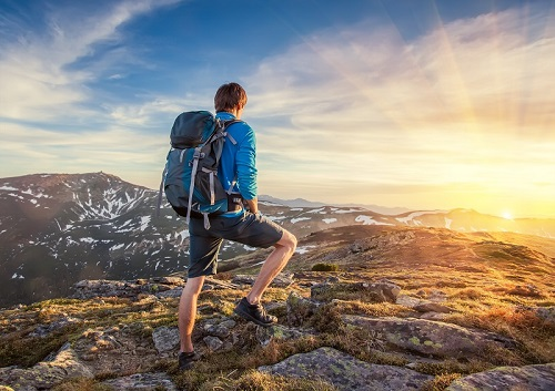 Man Standing on a Mountain with a Backpack Watching Sunset