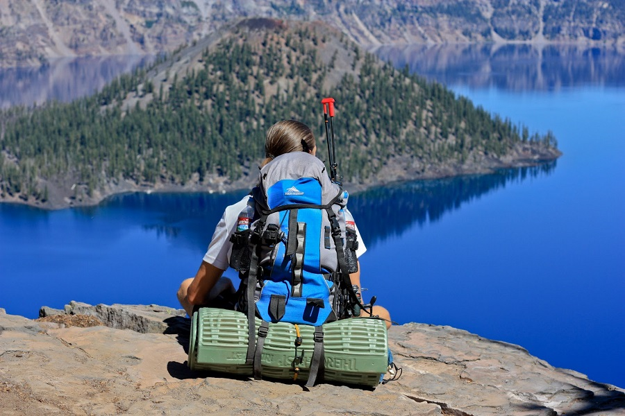 Woman Sitting on a LakeSide Ledge with a Backpack
