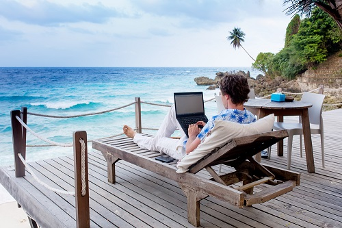 A Digital Nomad Laying on a Beach Working on a Laptop